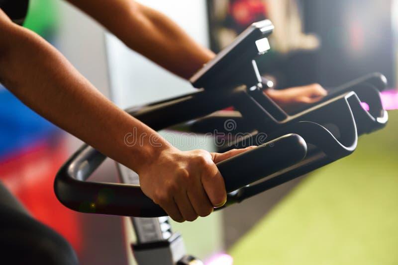Kvinna på en idrottshall som inomhus gör snurr eller cyclo med den smarta klockan royaltyfri foto