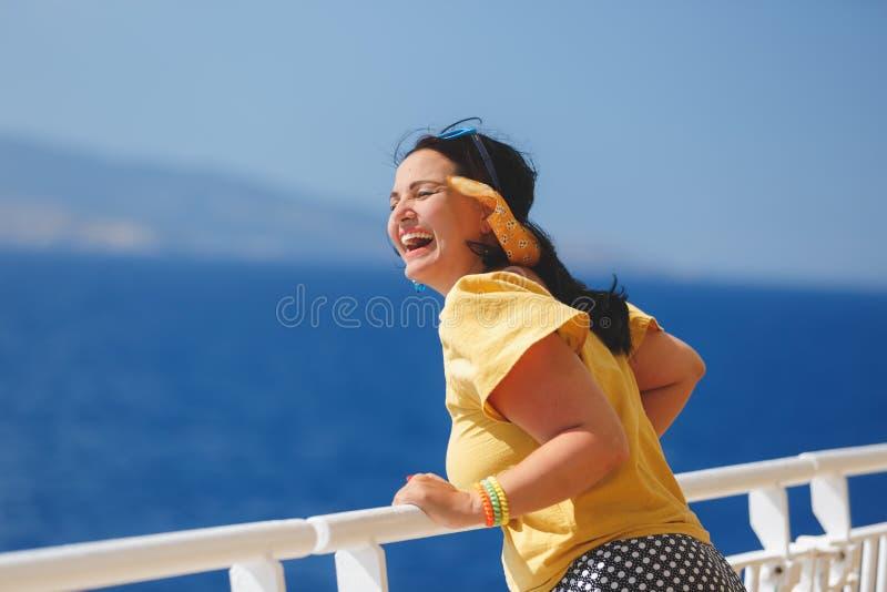 Kvinna på en kryssningsemester stå på däck av kryssningskeppet, stark vind som blåser hennes hår royaltyfria bilder