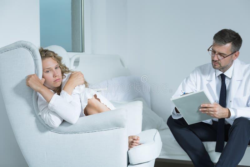 Kvinna på en period med en psykiater royaltyfri foto