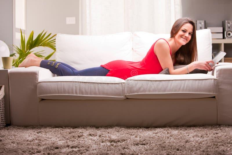 Kvinna på en soffa som tycker om innehållet på en minnestavla arkivfoto