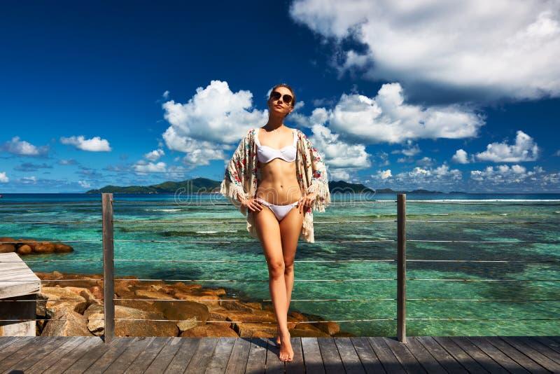 Kvinna på en strandbrygga på Seychellerna, La Digue royaltyfri bild
