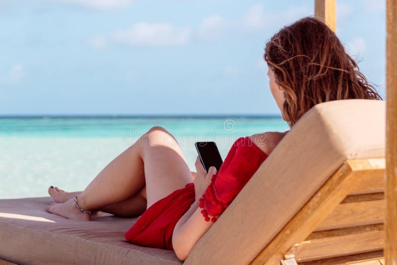 Kvinna på en sunchair i ett tropiskt läge genom att använda hennes smartphone Klart turkosvatten som bakgrund royaltyfri fotografi