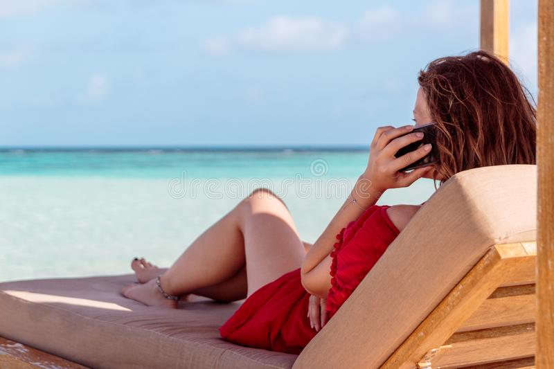 Kvinna på en sunchair i ett tropiskt läge som kallar vänner med smartphonen Klart turkosvatten som bakgrund arkivfoton