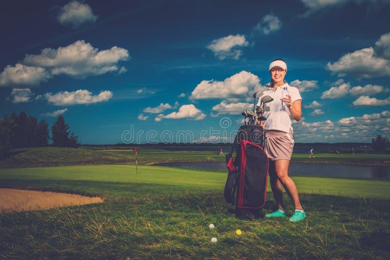 Kvinna på ett golffält royaltyfria bilder
