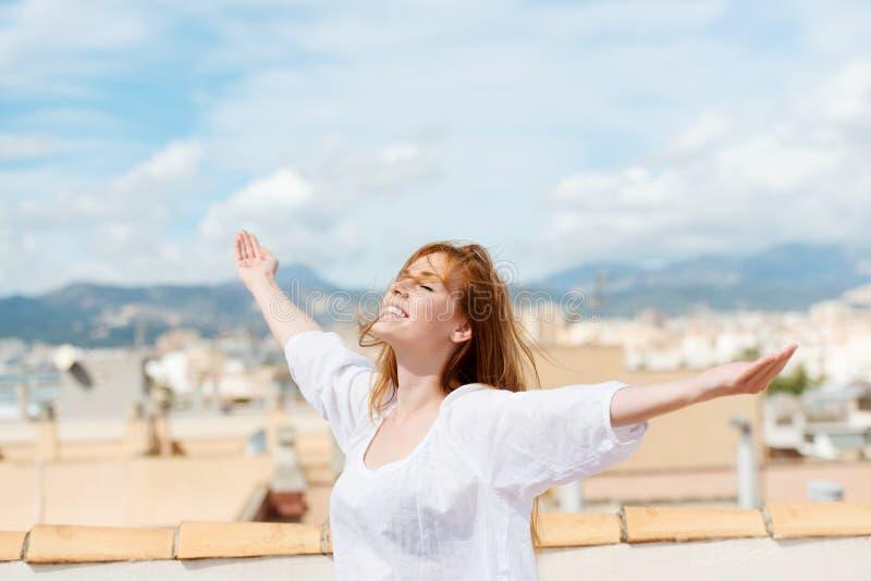 Kvinna på ett tak som omfamnar solskenet arkivbild
