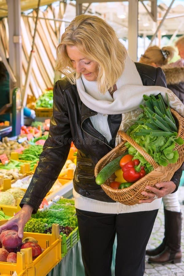 Kvinna på för marknadsplockning för öppen luft grönsaker arkivfoton