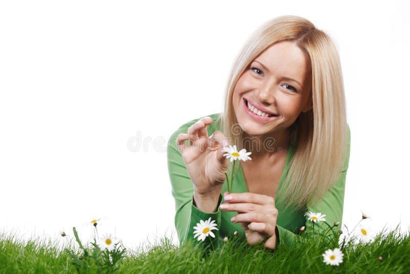 Kvinna på gräs med blommor arkivbild