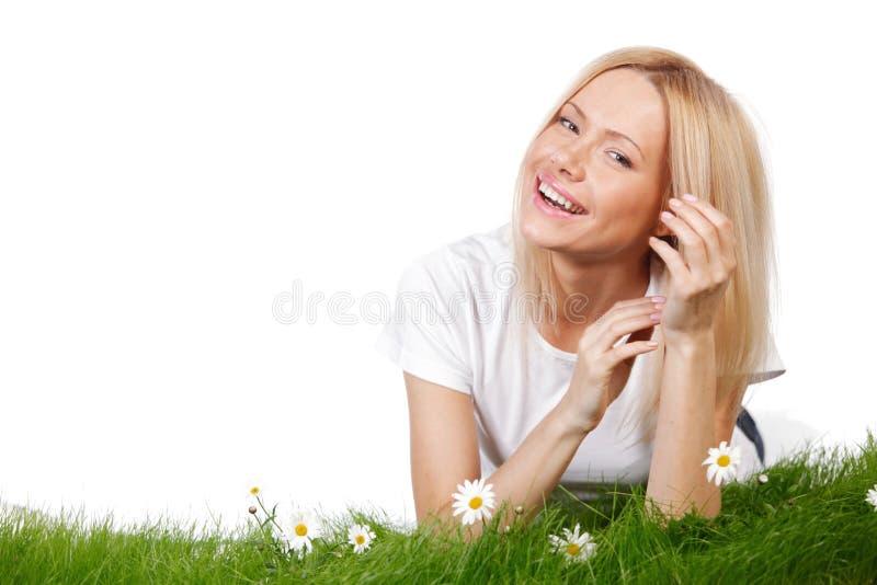 Kvinna på gräs med blommor arkivfoto