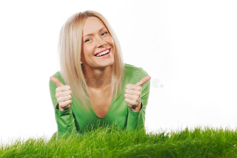 Kvinna på gräs med tummar upp arkivfoto
