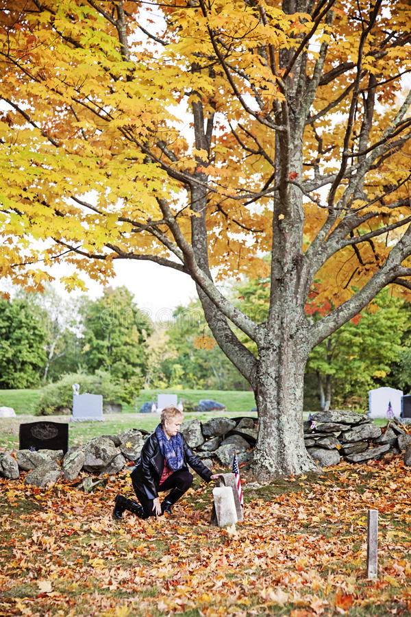 Kvinna på graven i kyrkogård royaltyfri fotografi