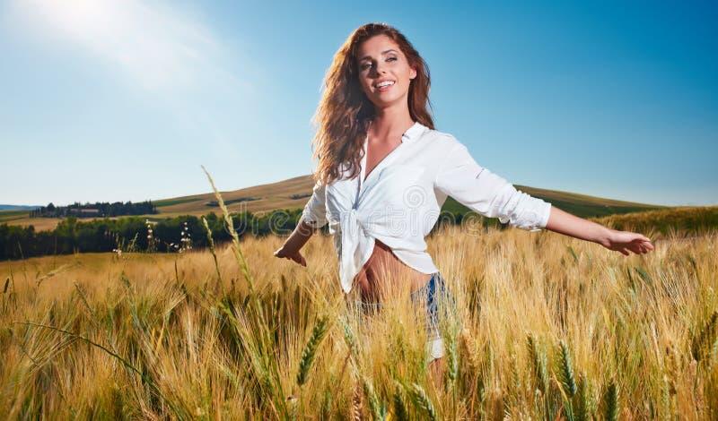 Kvinna på guld- sädes- fält i sommar arkivbilder