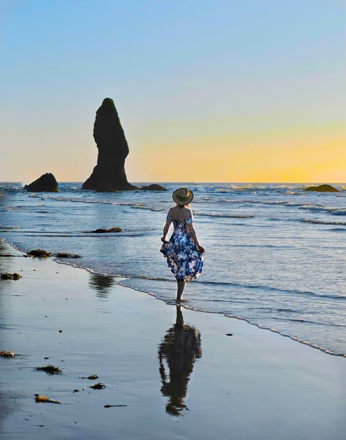 Kvinna på hållande ögonen på solnedgång för sandig strand över havet royaltyfri bild