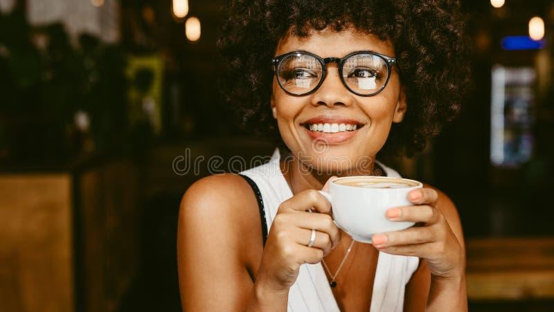 Kvinna på kafét som har kaffe arkivbild
