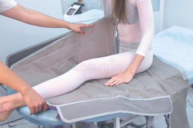 Kvinna på kliniken för behandlingen av tryckterapitillvägagångssättet Förbereda sig till tillvägagångssättet med en doktor royaltyfria foton