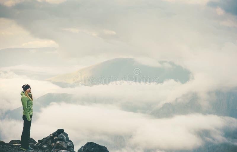 Kvinna på klipparesande som tycker om molniga dimmiga berg royaltyfri fotografi