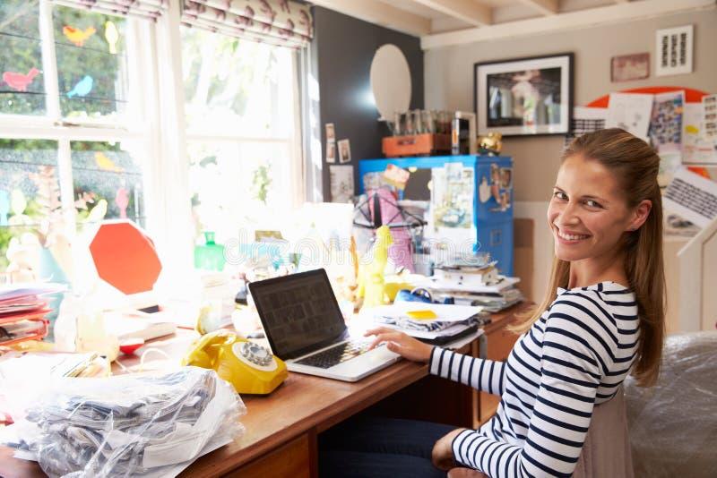Kvinna på kontor för affär för bärbar dator rinnande hemifrån arkivfoton