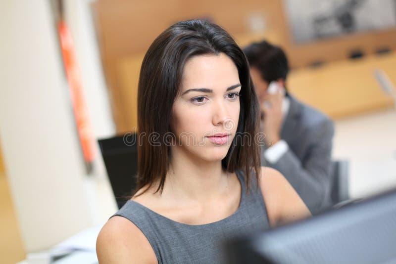 Kvinna på kontoret som arbetar på datoren arkivbild