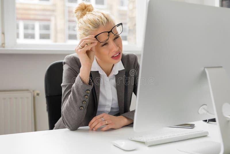 Kvinna på kontoret som ser datoren med henne sammanpressade ögon royaltyfri foto