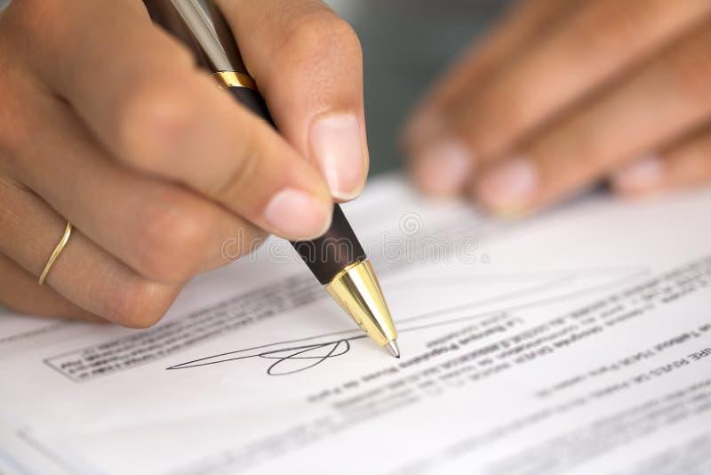 Kvinna på kontorsskrivbordet som undertecknar ett avtal med den grunda fokusen på si arkivfoton