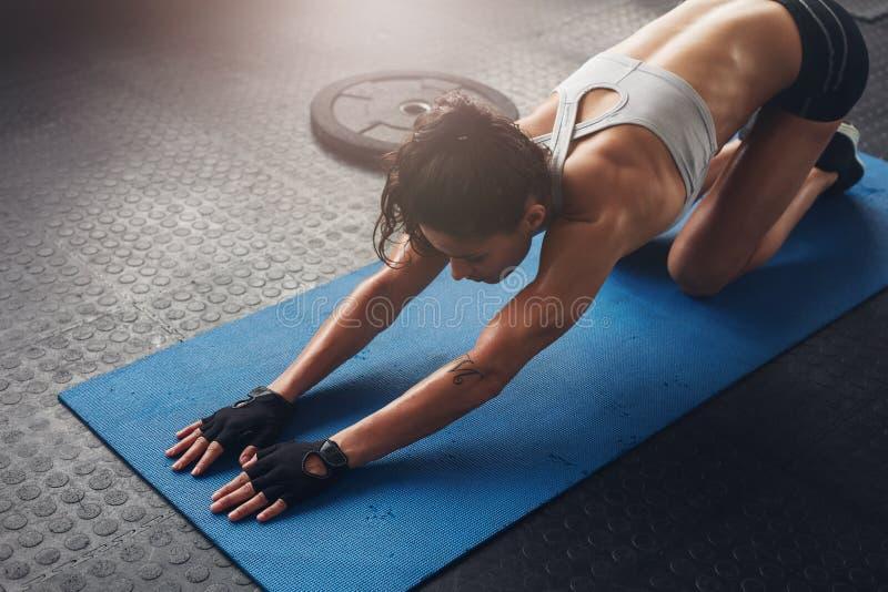 Kvinna på matt görande sträckande genomkörare för kondition på idrottshallen royaltyfri foto