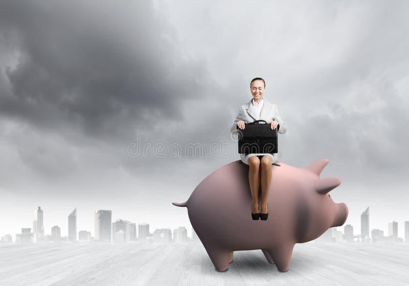 Kvinna på moneybox royaltyfri foto