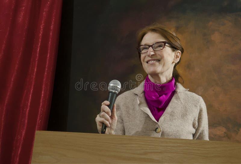 Kvinna på podiet med mikrofonen arkivfoto