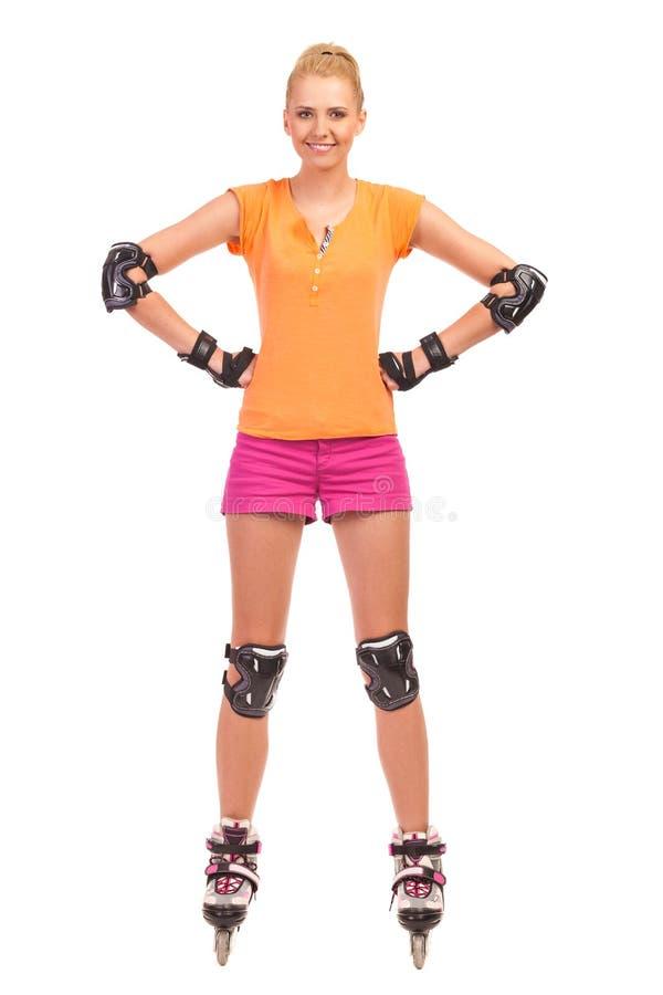 Kvinna på rollerblades som står med händer på höfter. arkivbild