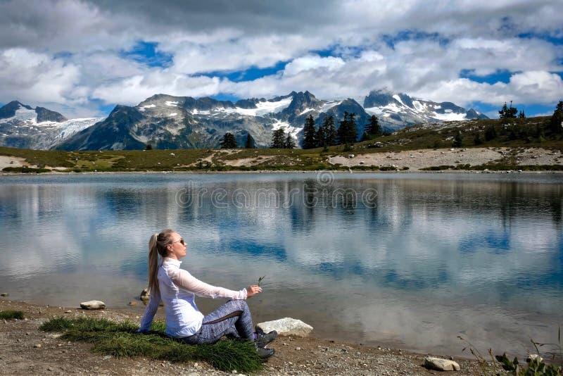 Kvinna på sjökusten som mediterar och kopplar av Härlig sikt av berg och reflexioner i sjön royaltyfri foto
