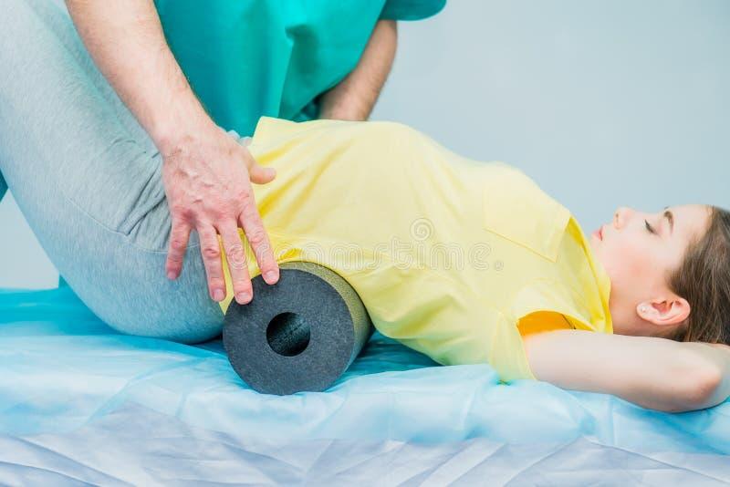Kvinna på sjukgymnastiken som gör fysiska övningar med hennes terapeut, dem som använder en massagerulle En kiropraktor behandlar royaltyfri bild