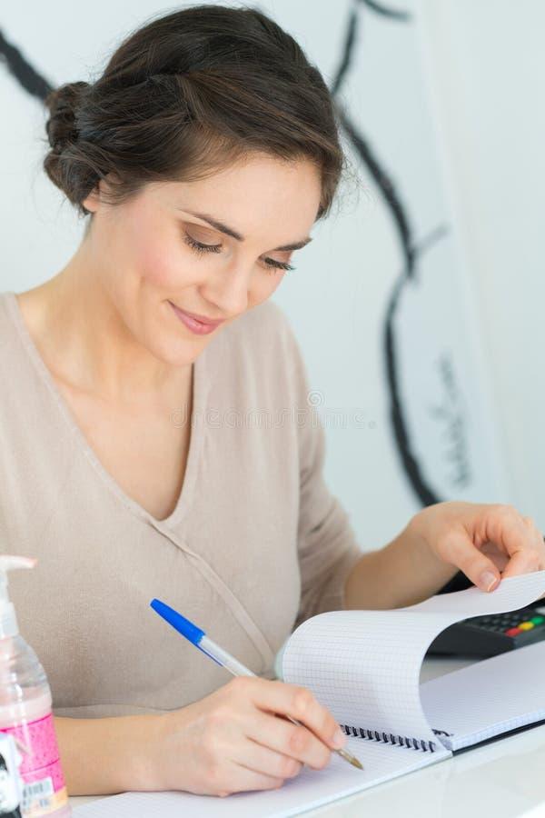 Kvinna p? skrivbordhandstil i anteckningsbok royaltyfria foton