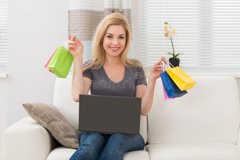 Kvinna på Sofa With Laptop And Shopping påsar arkivfoto