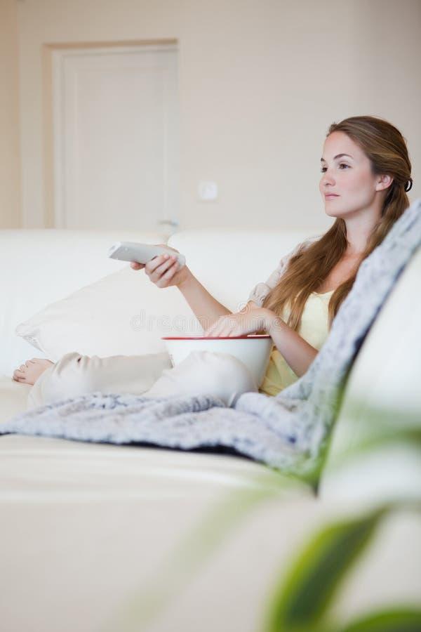 Kvinna på sofaen som tycker om en film med popcorn arkivfoton