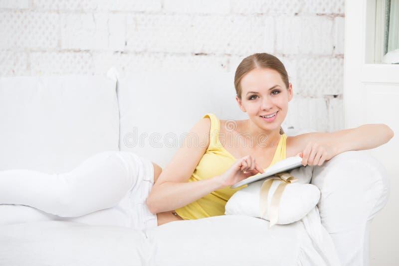 Kvinna på soffan och den rörande elektroniska minnestavlan royaltyfri fotografi