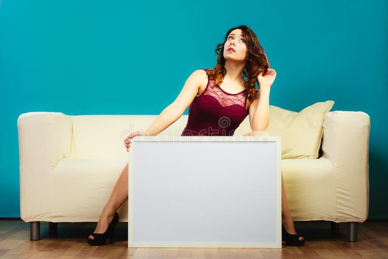 Kvinna på soffan som rymmer brädet för tom presentation fotografering för bildbyråer