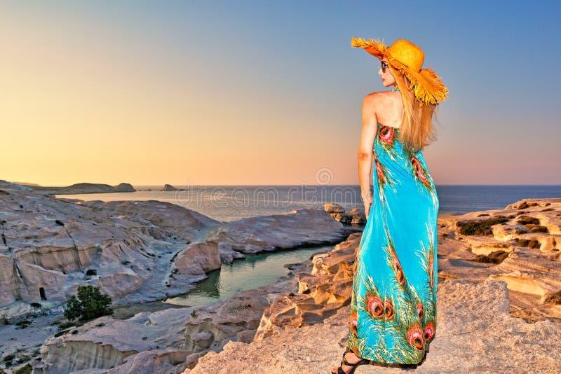 Kvinna på solnedgången på Sarakiniko i Milos, Grekland royaltyfri fotografi