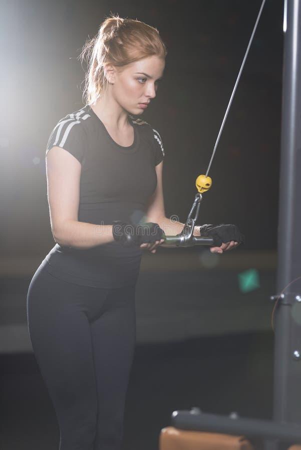 Kvinna på sportidrottshallen som gör armövningar på en maskin royaltyfria bilder