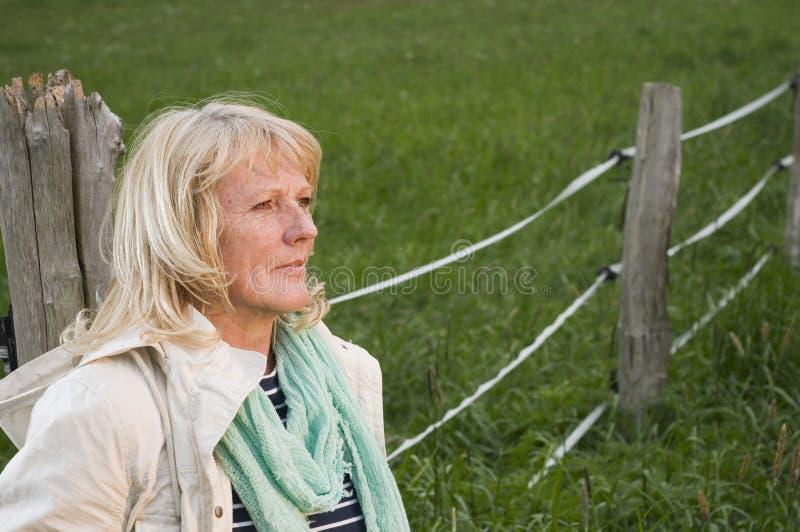 Kvinna på staketblicken bort royaltyfri bild