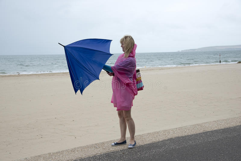 Kvinna på stranden som öppnar ett paraply fotografering för bildbyråer