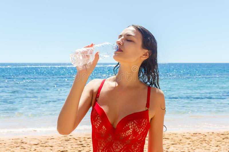 Kvinna på stranden som dricker ett kallt vatten i flaska Kvinnlig i röd bikini som tycker om drinken för isvatten som ler lycklig royaltyfri bild