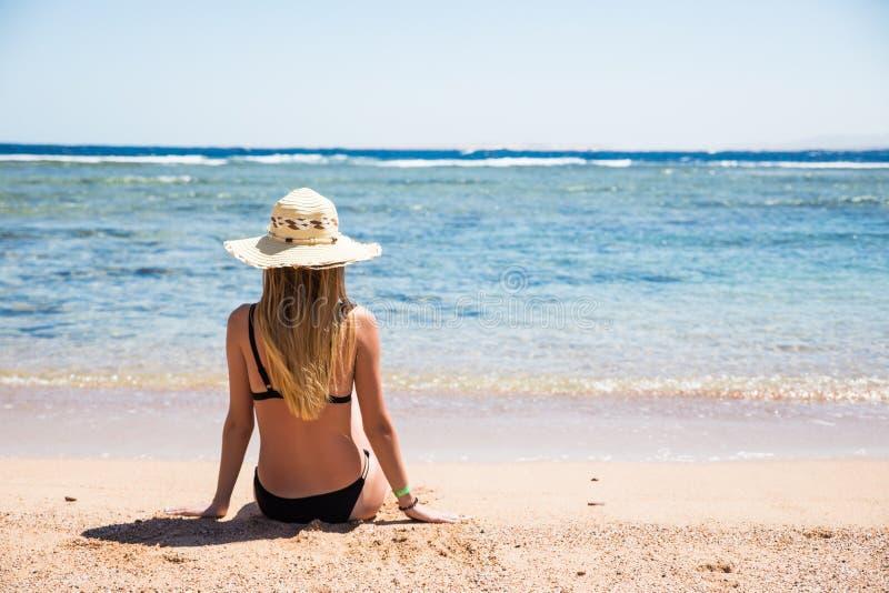 Kvinna på strandsammanträde i sand som ser havet som tycker om flykt för sol- och sommarloppferiesemester Flicka, i att koppla av arkivbild