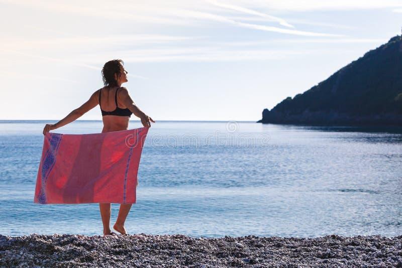 Kvinna på täckande höfter för strand med handduken royaltyfri fotografi