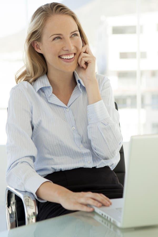 Kvinna på telefonen på arbetsplatsen - använda mobiltelefonen royaltyfria bilder