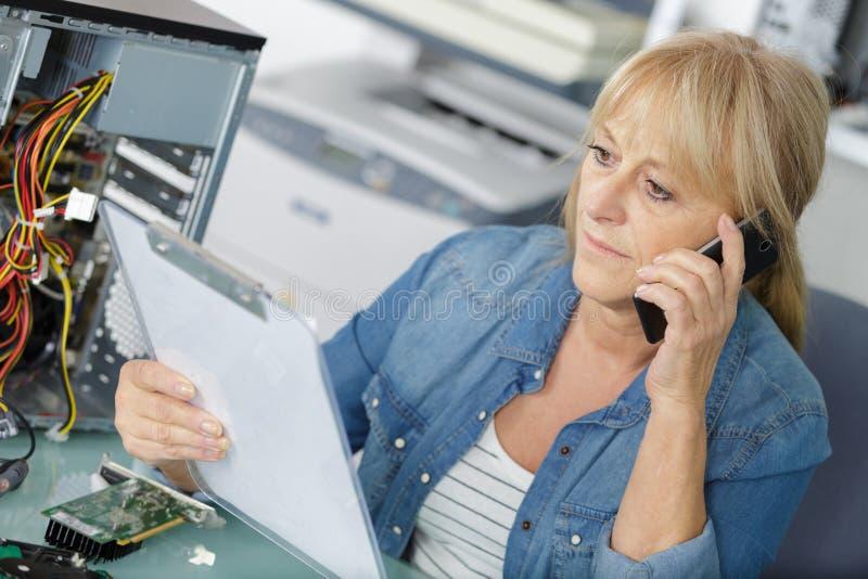 Kvinna på telefonen som talar om faktura med kunden royaltyfri bild