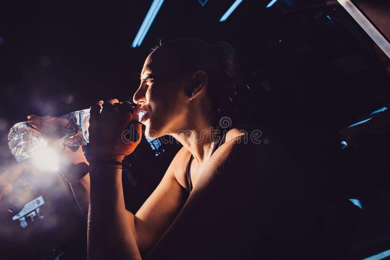 Kvinna på trampkvarndricksvatten, medan öva i idrottshall royaltyfria bilder