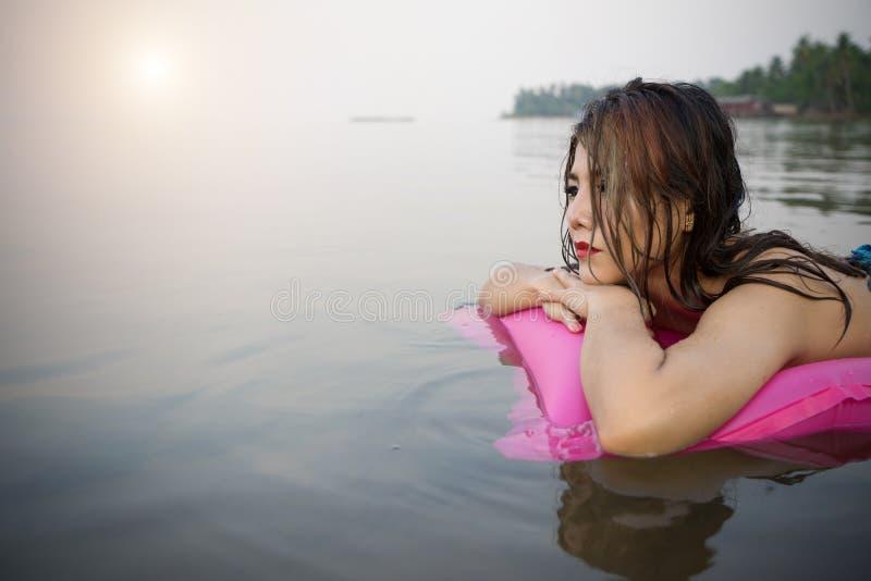 Kvinna på uppblåsbar simbassängsäng som tycker om att garva för sol royaltyfria foton