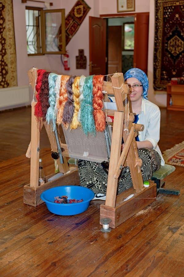 Kvinna på vävstolen i visningslokalen av mattfabriken i Denizli, Turkiet royaltyfri foto