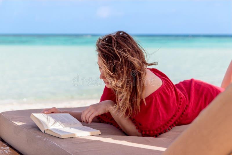 Kvinna p? en sunchair som l?ser en bok i ett tropiskt l?ge Klart turkosvatten som bakgrund arkivbild