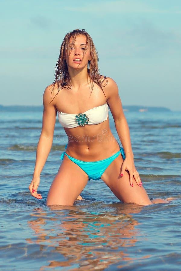 Kvinna p? havet i en vit bikini royaltyfri foto