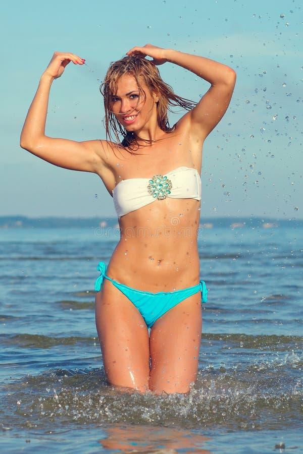 Kvinna p? havet i en vit bikini royaltyfri bild