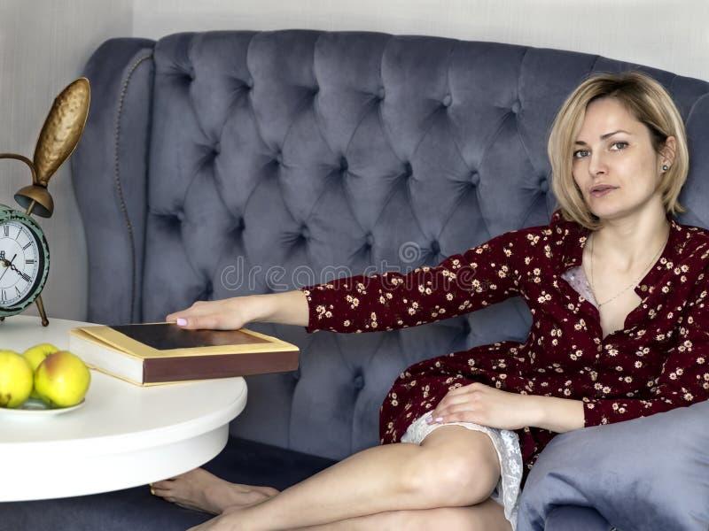 Kvinna p? soffan i rummet arkivbild